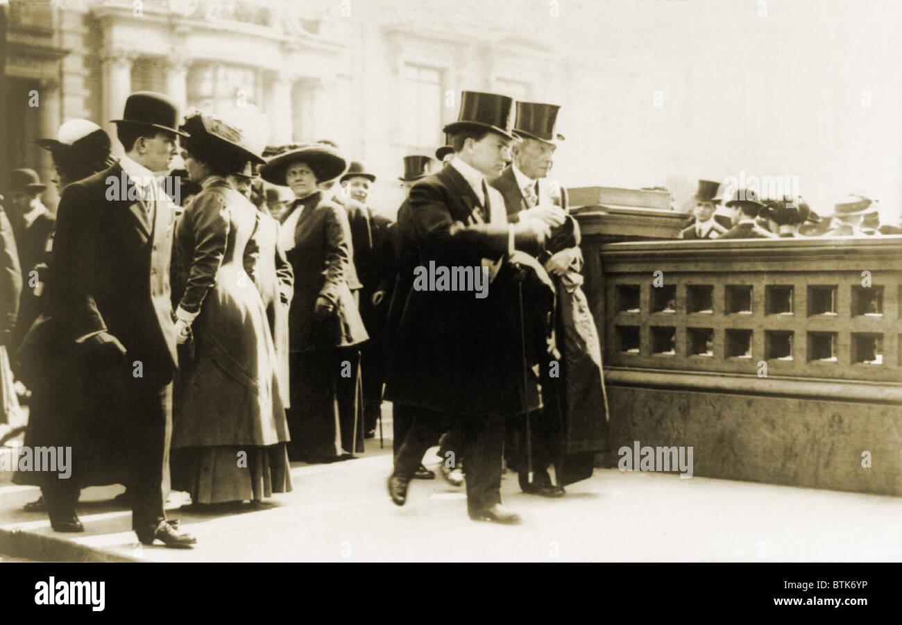 John Davison Rockefeller (1839-1937), walking with his son John D. Jr., in New York as onlookers watch the pair. - Stock Image