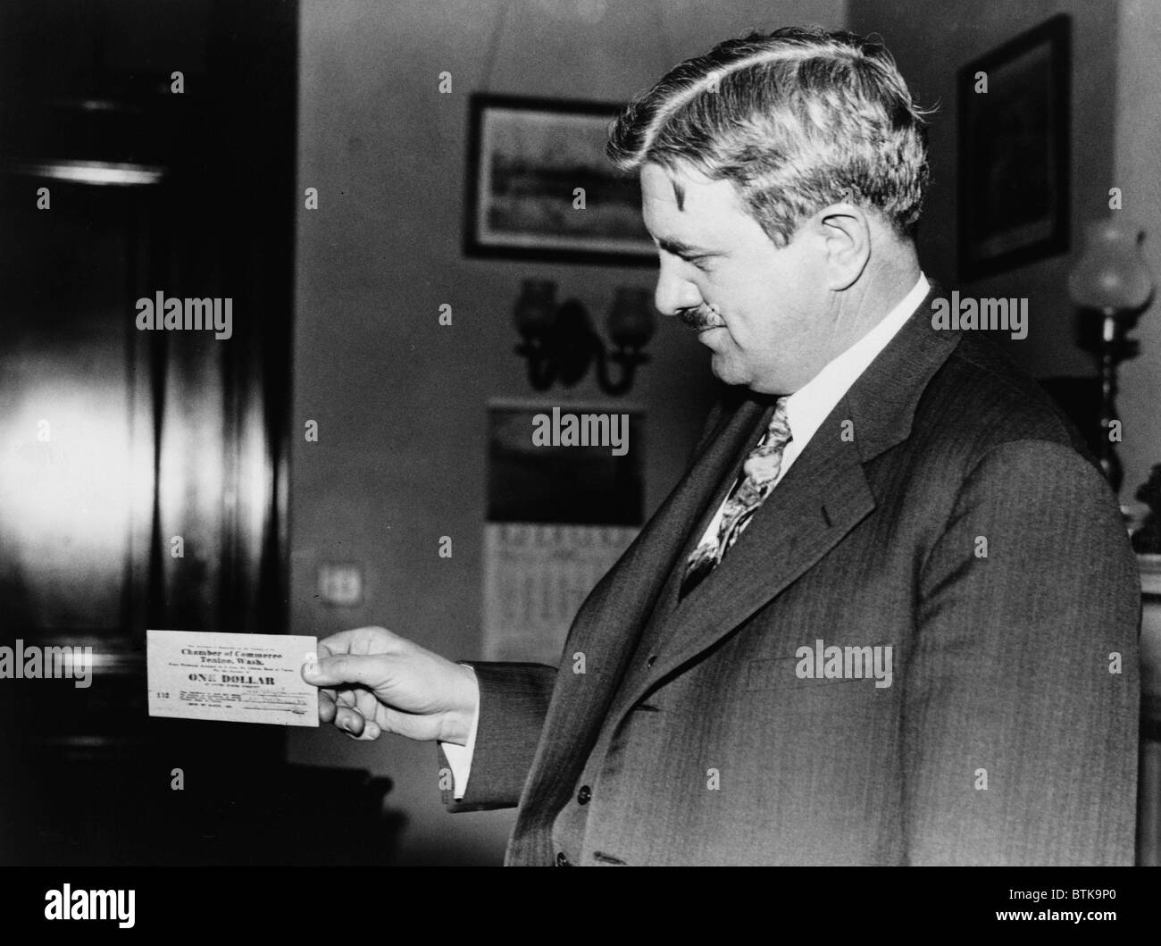 Senator Clarence C. Dill of Washington state, holding one of the wooden dollars used by town of Tenino, Washington. - Stock Image