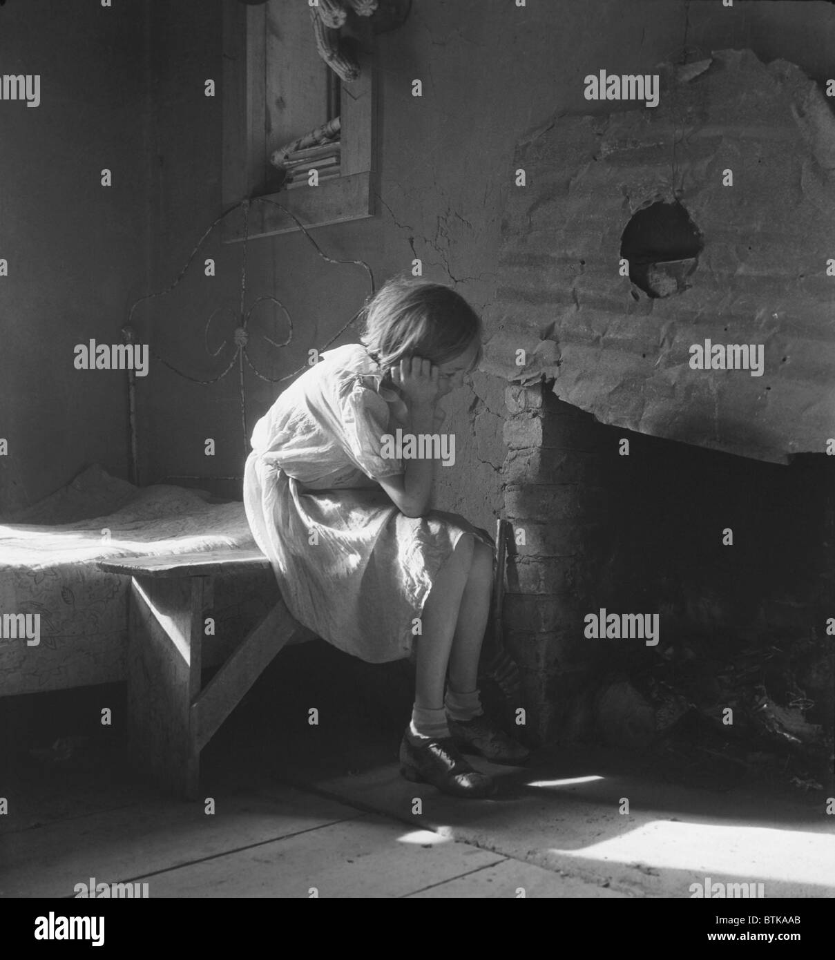 The Great Depression. Young girl sitting on bench near fireplace with bed in background in a Taos, New Mexico, resettlement - Stock Image