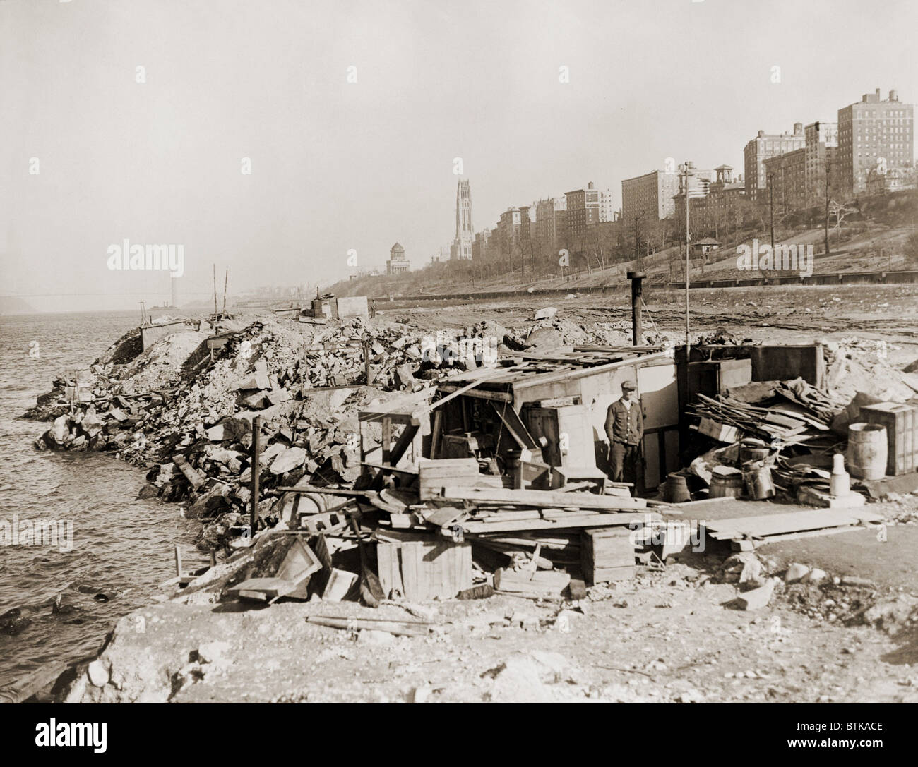 An unemployed a man standing near his hut in a New York City shanty town during the Great Depression. In the background - Stock Image