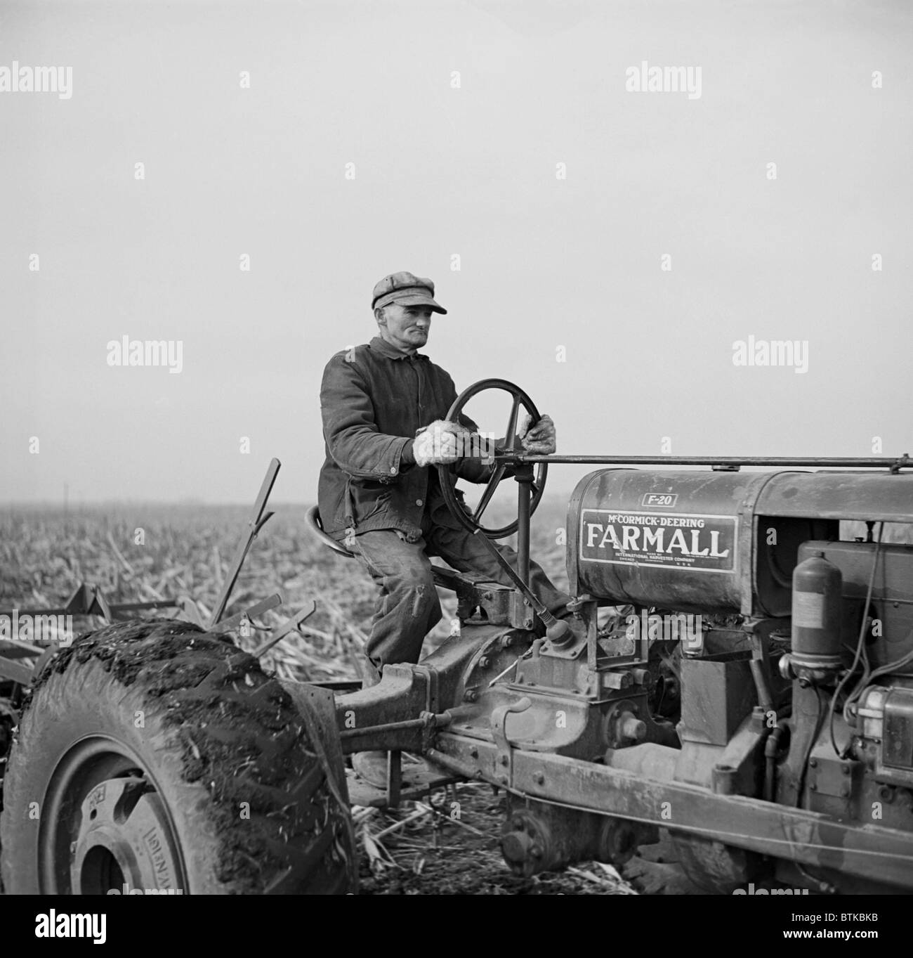 Tip Estes, a hired hand on an Indiana Farm, operating a tractor. The father of nine children, he lived in a small - Stock Image