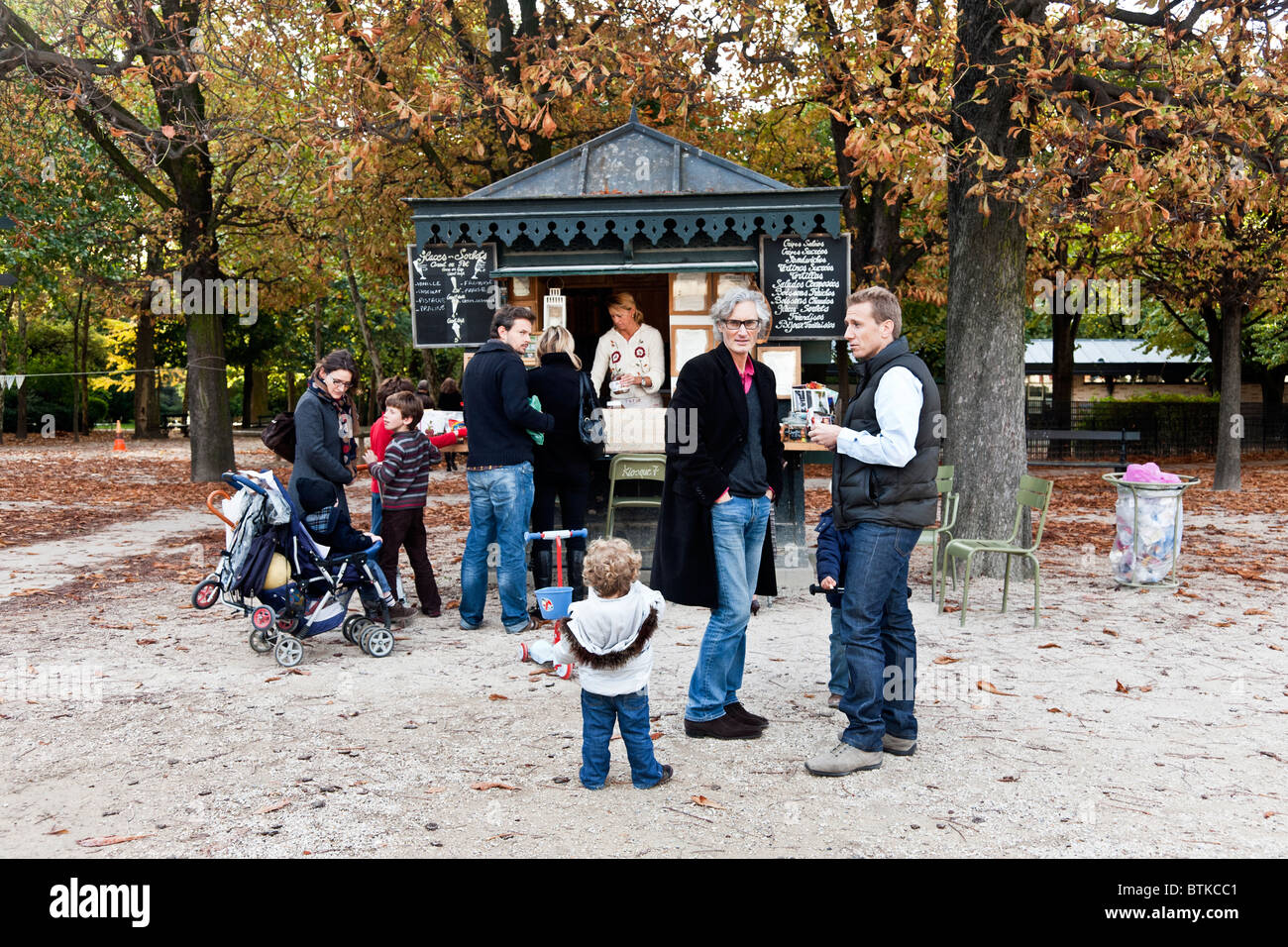 Parisian parents with young children cluster around ice cream kiosk in Luxembourg Gardens on beautiful autumn Sunday - Stock Image