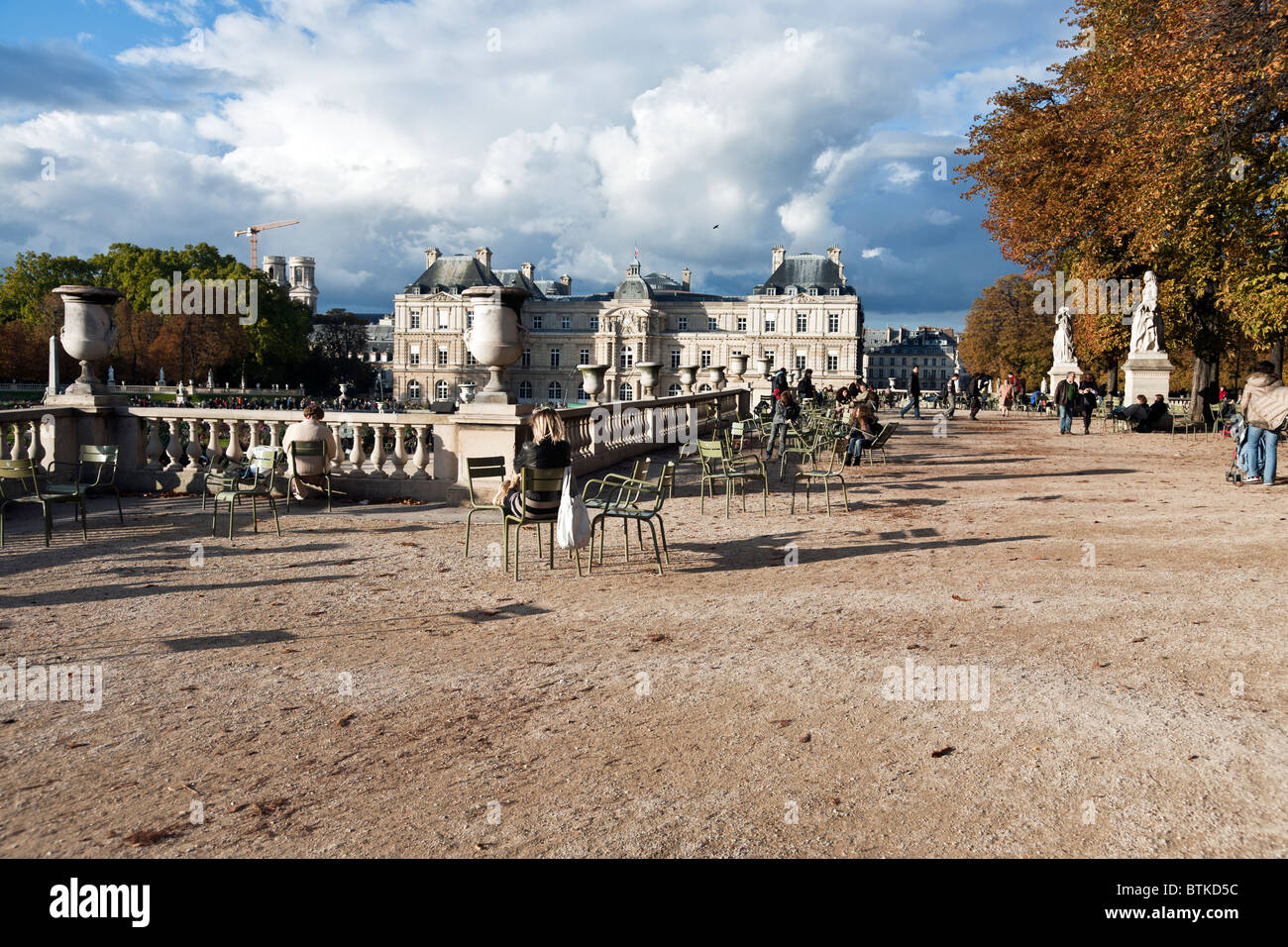 people enjoy beautiful autumn afternoon on terrace of Luxembourg Gardens with statuary urns & balustrade overlooking - Stock Image