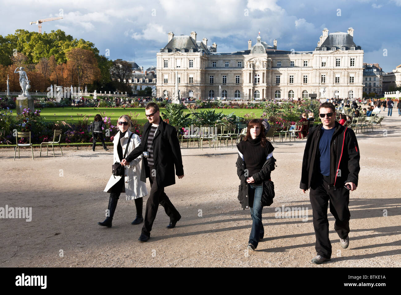 two young Parisian couples walking briskly in the gardens fronting the Luxembourg Palace on a beautiful autumn Sunday - Stock Image