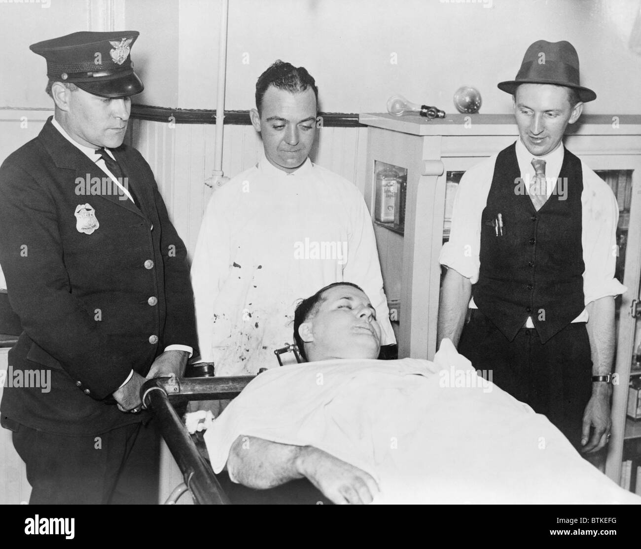 Dead body of Charles 'Pretty Boy' Floyd (1904-1934) on a gurney with police officers Robert Pyle and George - Stock Image