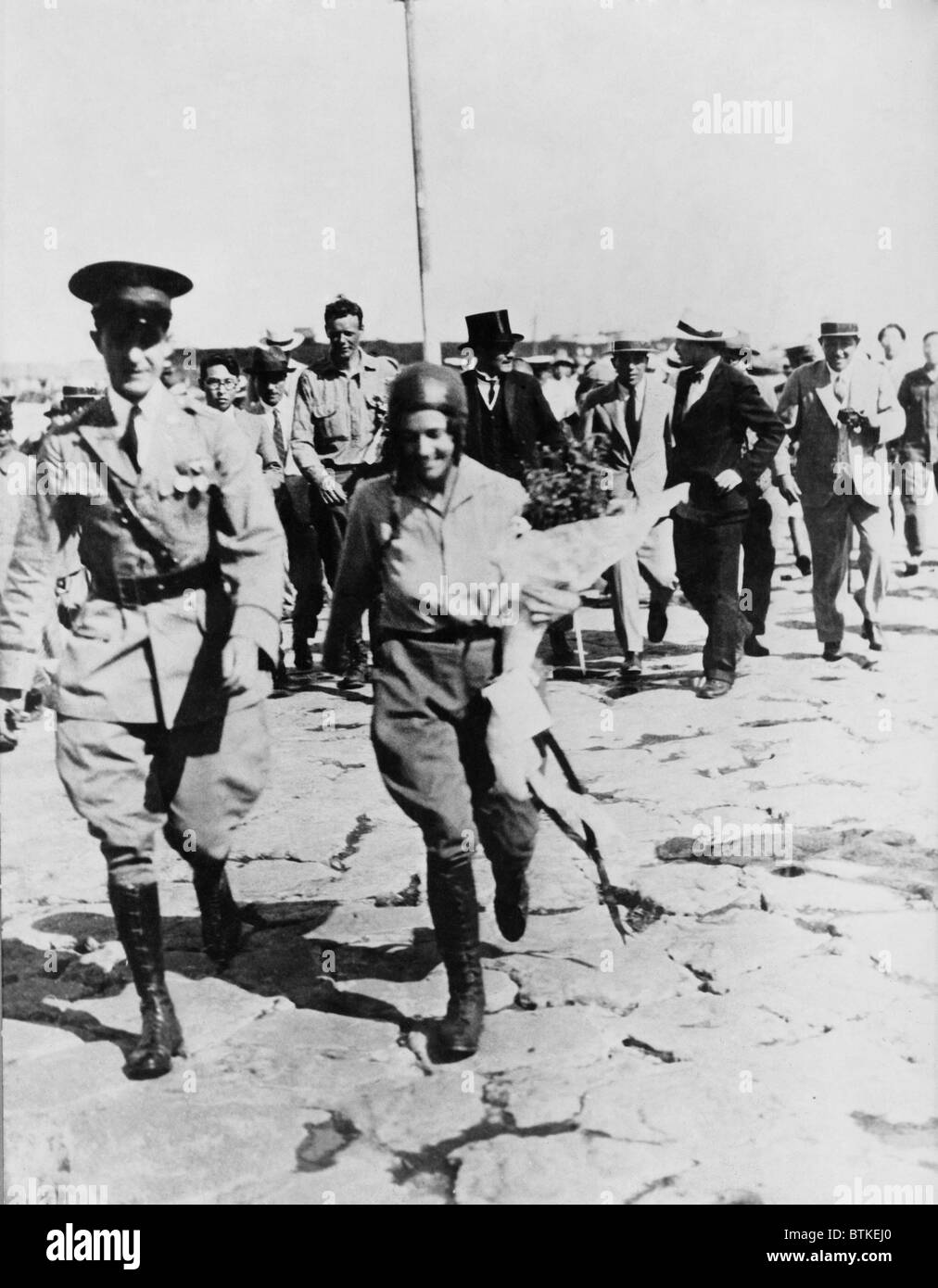 Mrs. Anne Morrow Lindbergh escorted by Japanese officer, with her husband, Charles (in background) after their arrival - Stock Image