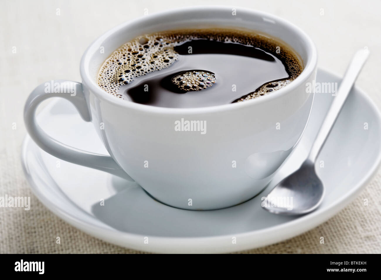 cup of freshly brewed black coffee, focus is on the middle bubbles - Stock Image
