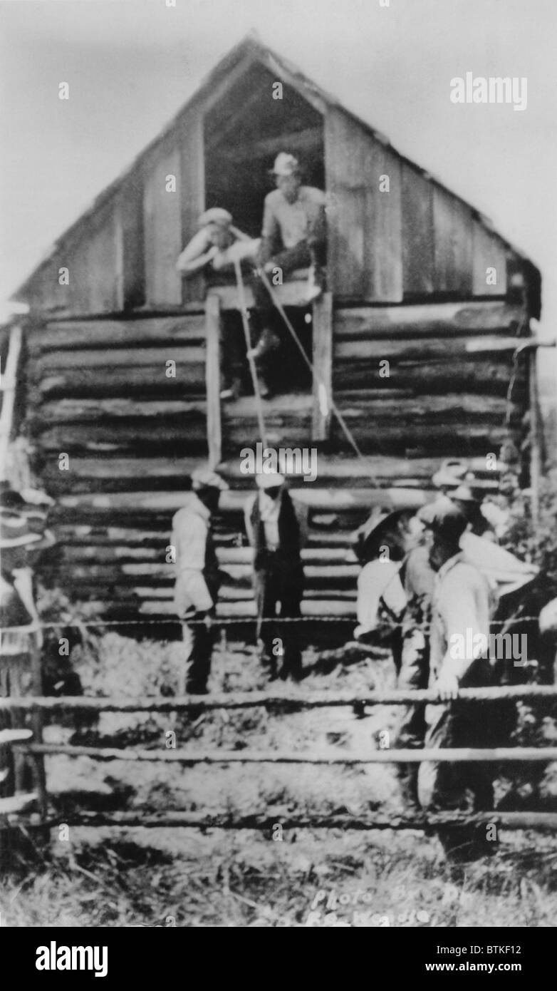 Photographic postcard of a few men preparing to lynch African American man by hanging from a barn.  Unlike most - Stock Image