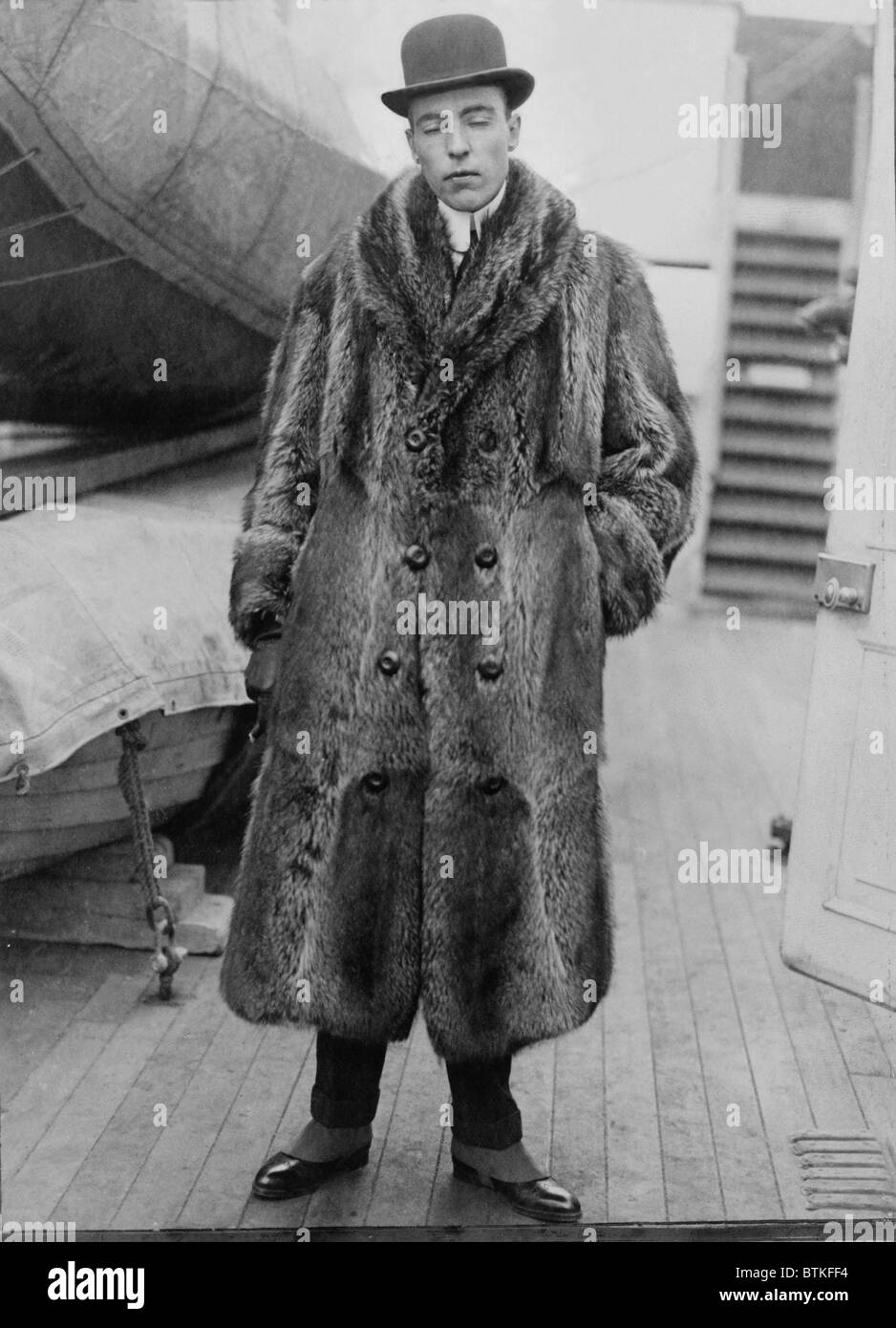 Vincent Astor (1891-1959), on deck of ship wearing fur coat. After his father, John Jacob Astor IV, died in the - Stock Image