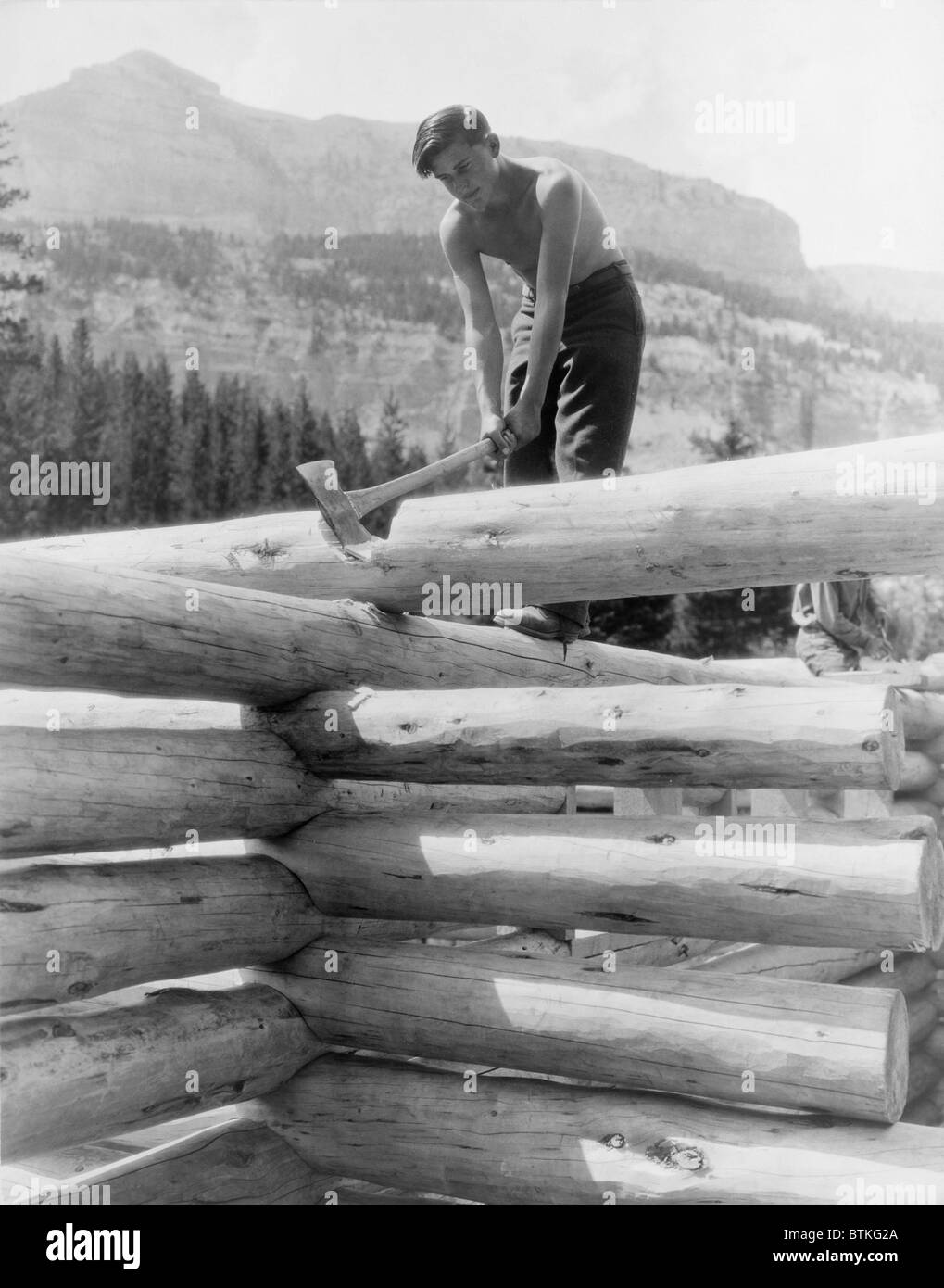 Civilian Conservation Corp worker cutting a coped joint on log cabin at Granite Creek, Teton National Forest, Wyoming - Stock Image