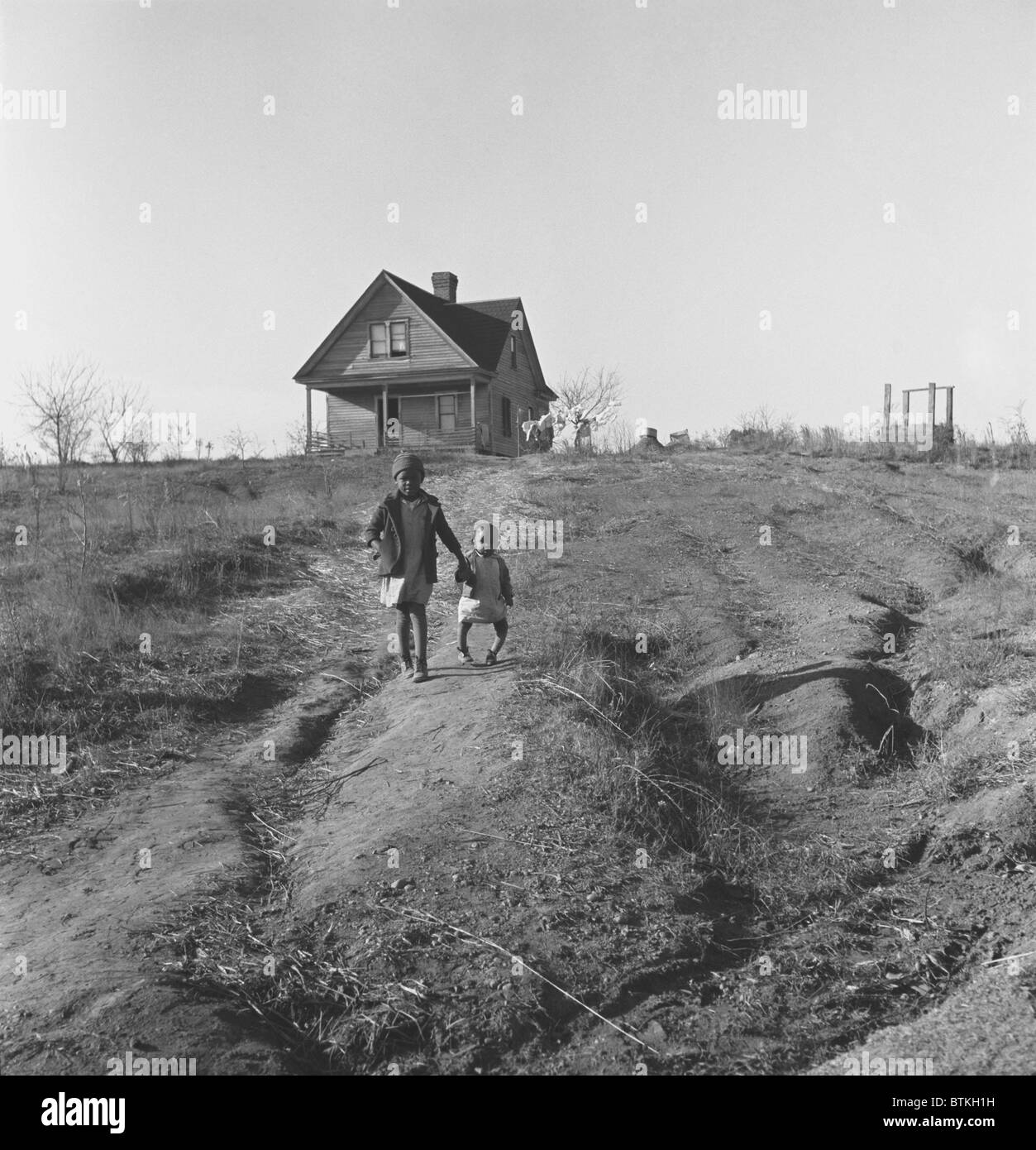 African American children walk from their old home on badly eroded land during the Great Depression. The older child - Stock Image