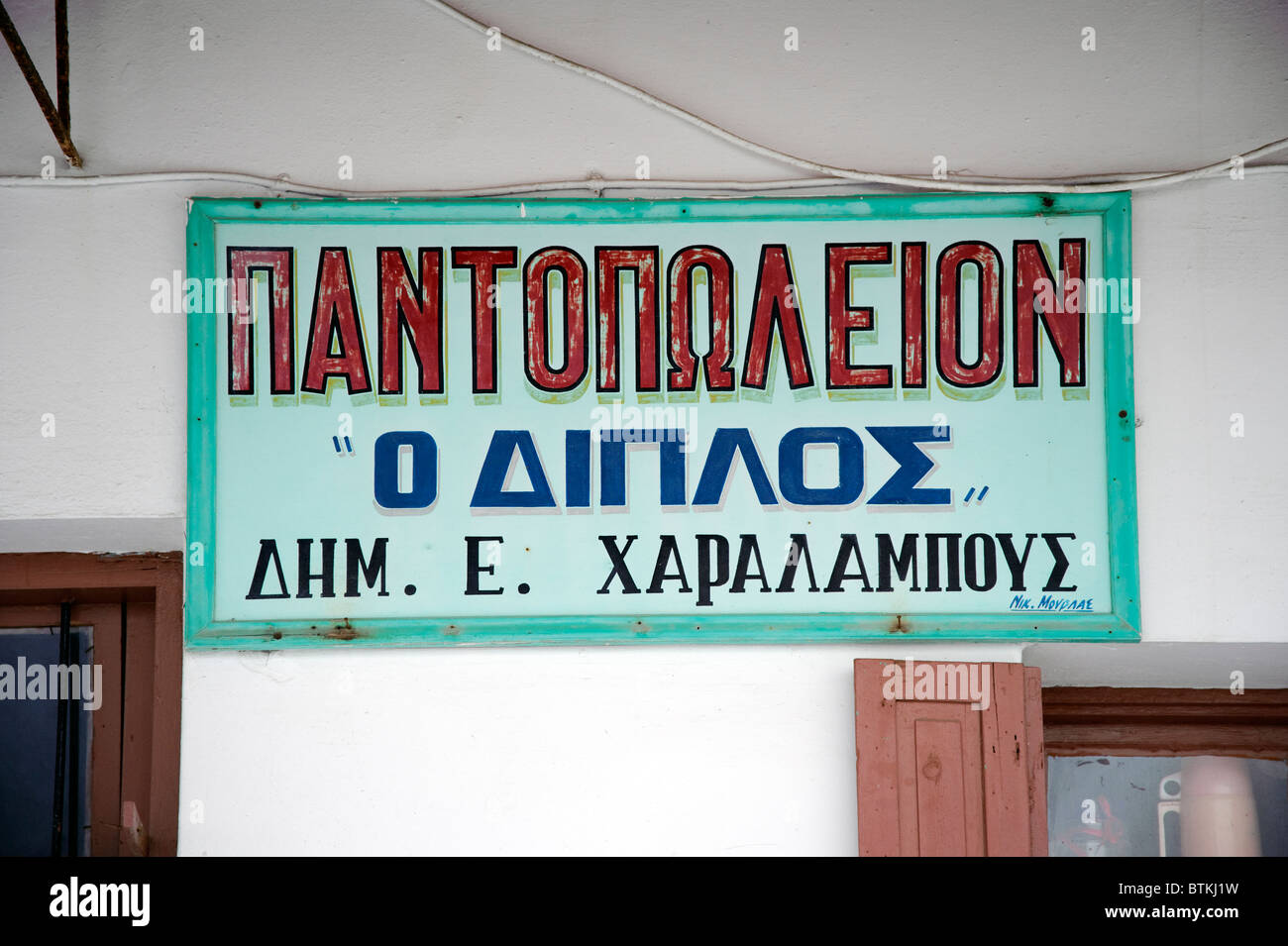 Greek shop sign on the facade of a general store in Parikia, on the Greek Cyclade island of Paros. - Stock Image