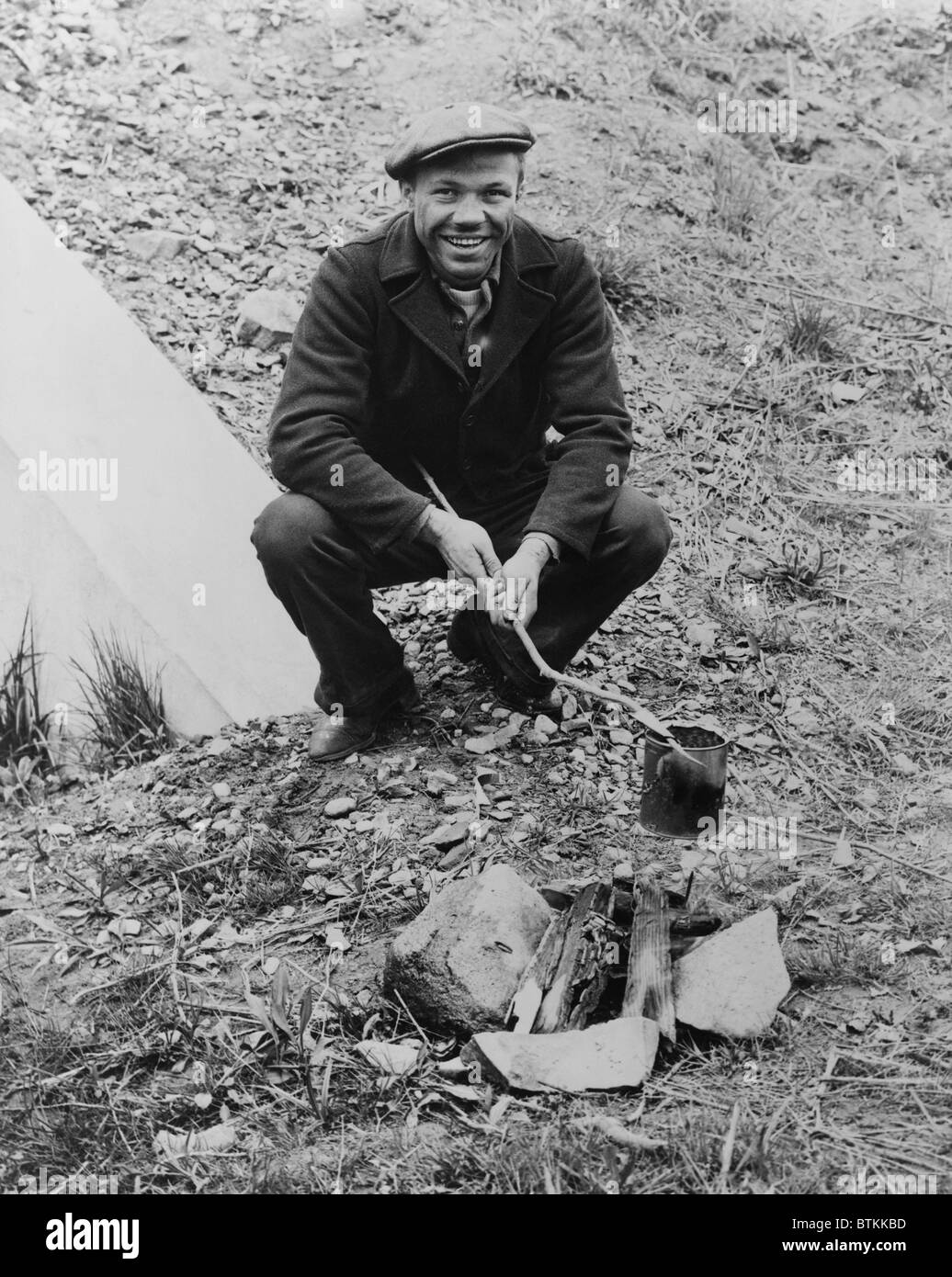 Hobo, Lou Ambers, cooking over a campfire with a tin can on a stick, during the Great Depression. 1935. - Stock Image