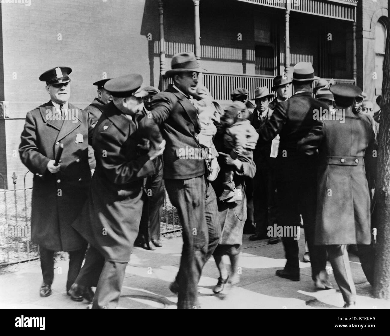 Washington D.C. Police arrest a man carrying child as others look on during a Depression era protest of unemployed. - Stock Image