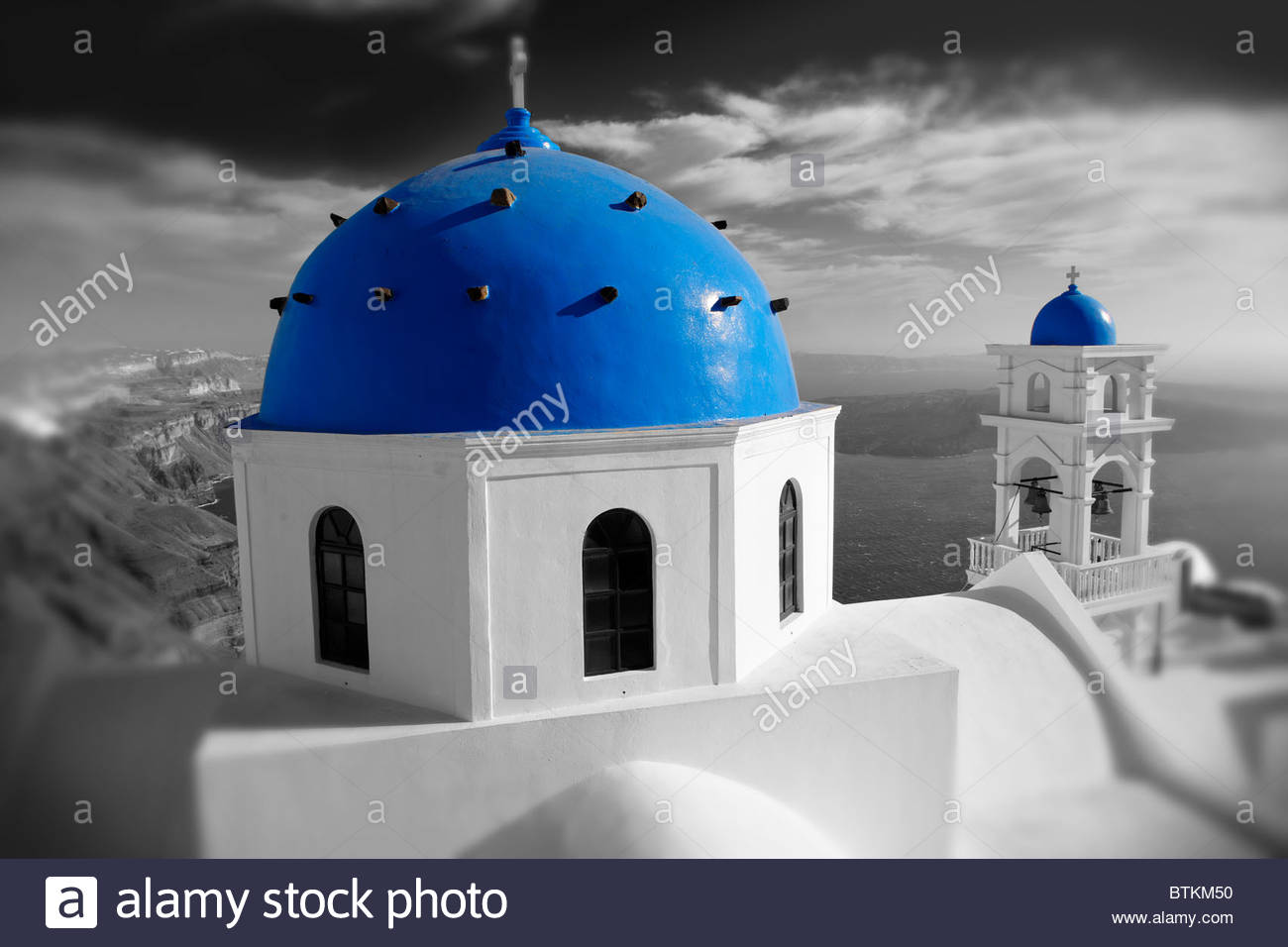 Selective colour photo of a traditional blue Domed church of Imerovigli looking across the sea, Santorini, Greece - Stock Image