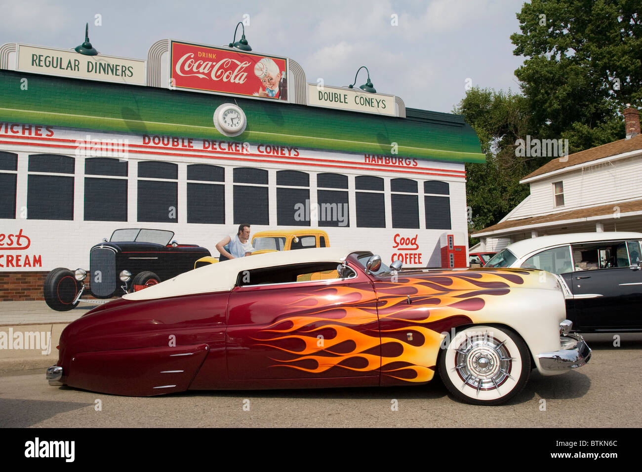 Auto- 1950 Mercury customized at Franklin, Ohio, USA, car show. Building with painted diner mural and Coca Cola Stock Photo