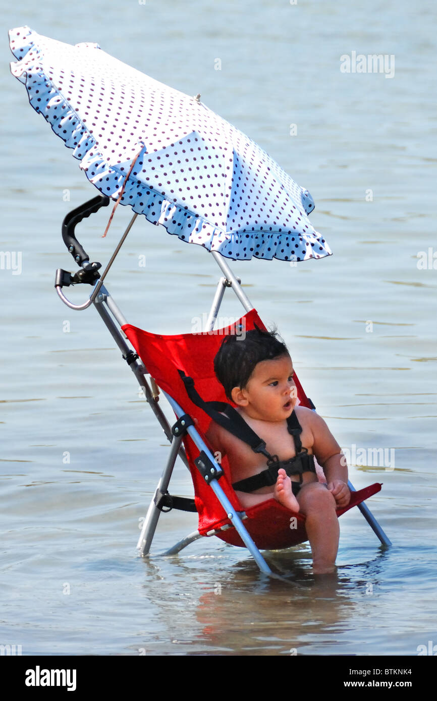 Baby in shallow sea on a hot day, mum close by - Stock Image