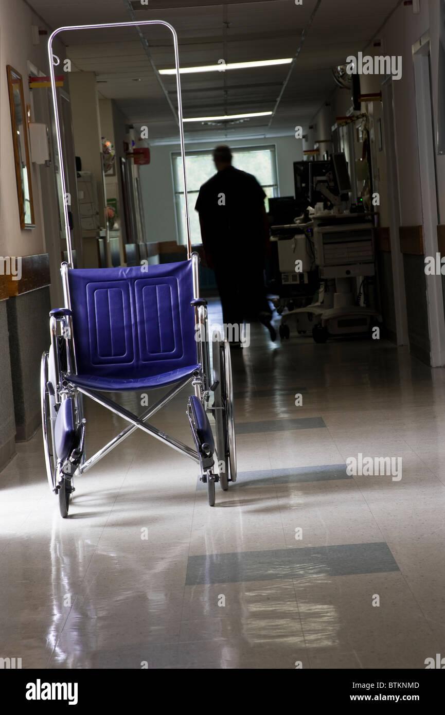 Empty Wheelchair In Hospital Corridor - Stock Image