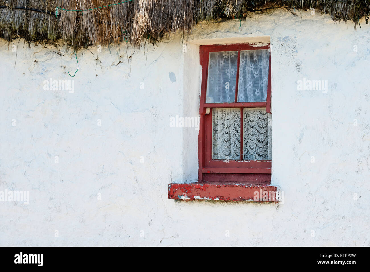 Window in a whitewashed, thatched cottage, Onacht, Inishmore, Aran Islands, County Galway, Ireland. - Stock Image