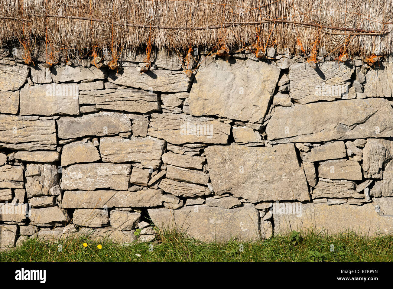 Dry stone house wall and thatch. Onacht, Inishmore, Aran Islands, County Galway, Connaught, Ireland. - Stock Image
