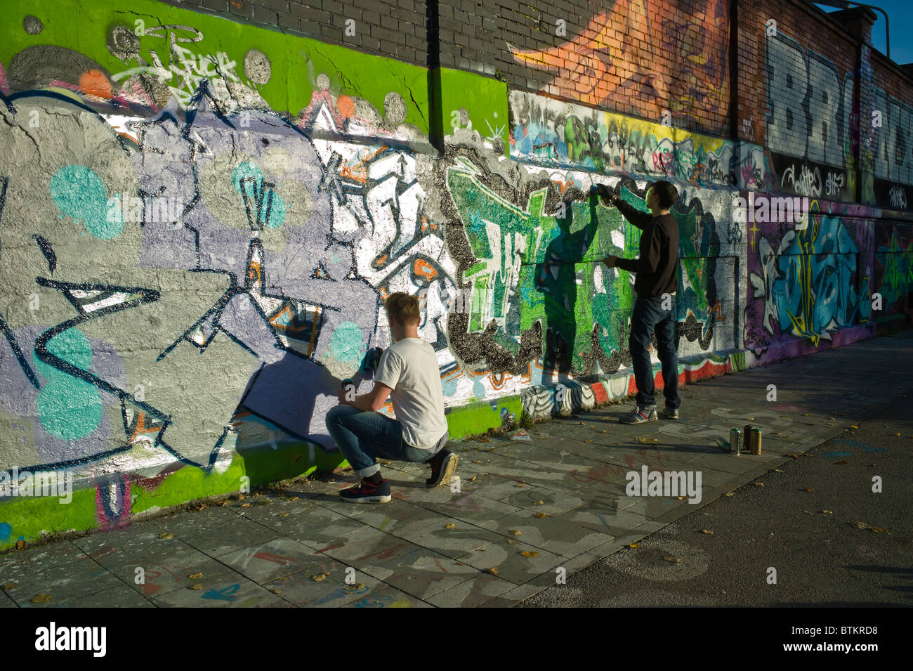 two graffiti artists working on a piece in munich germany stock