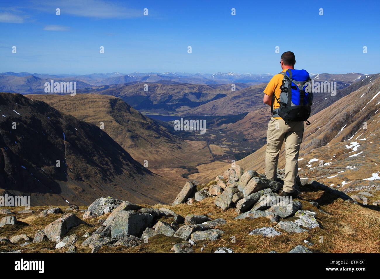 Hillwalker on Beinn Maol Chaluim looking down to the village of Glencoe. - Stock Image