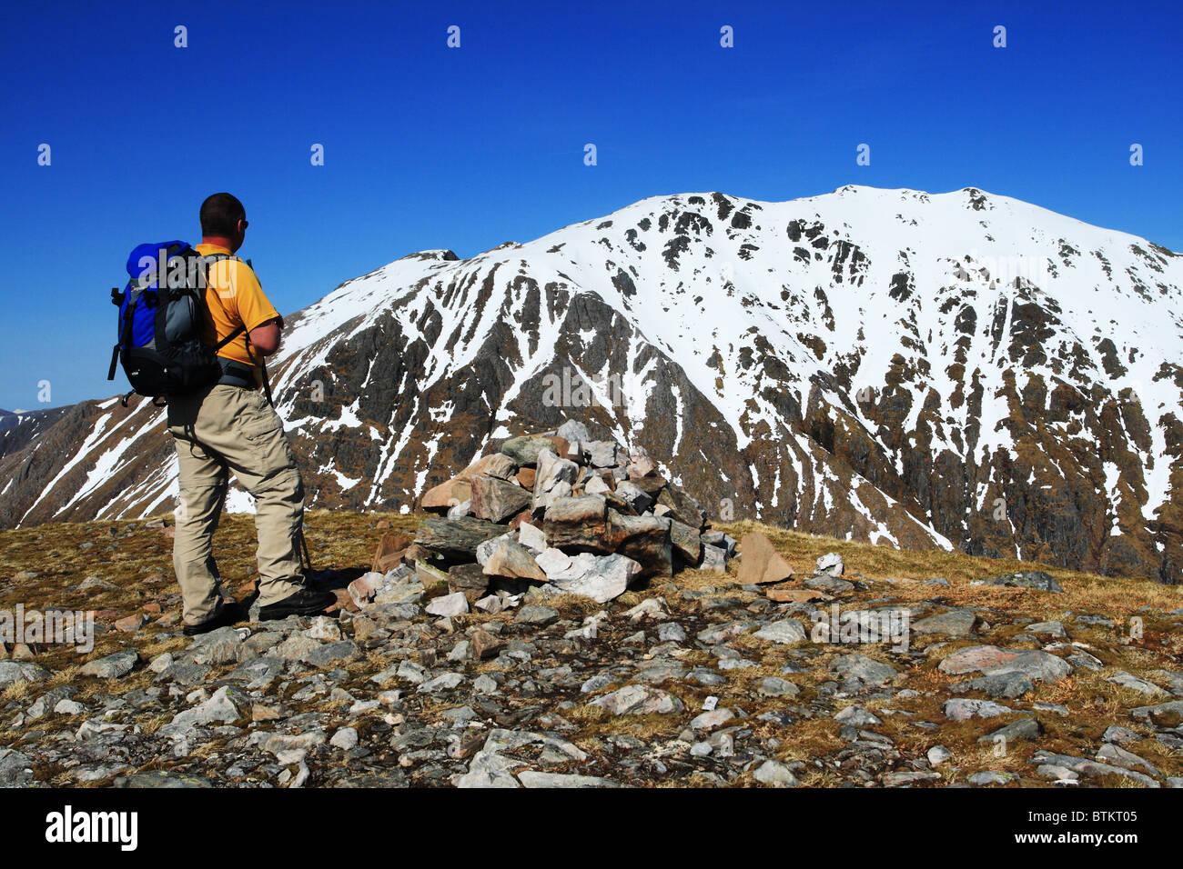 Hillwalker on the summit of Beinn Maol Chaluim looking across to Bidean nam Bian. - Stock Image