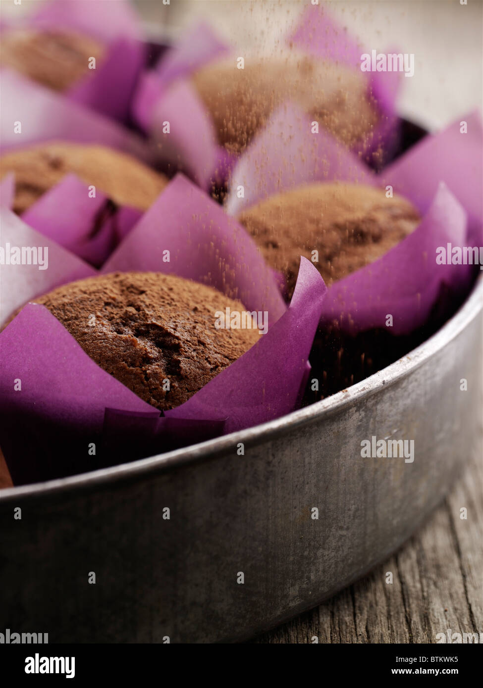 Fresh baked chocolate cupcakes in purple wrappers. - Stock Image