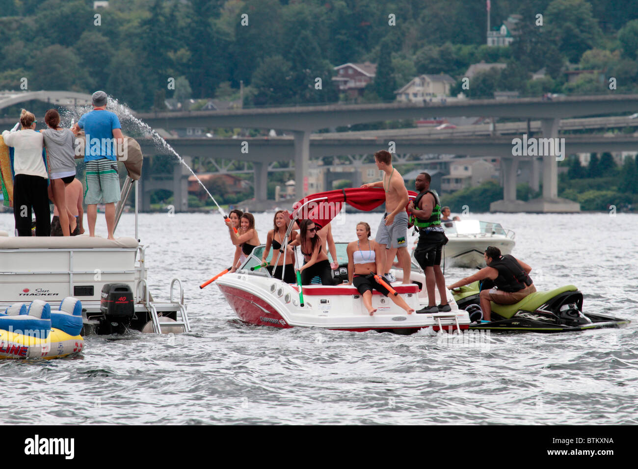 Seattle boaters partying on the water at Seafair watching the Blue Angels air show playfully squirting another group - Stock Image