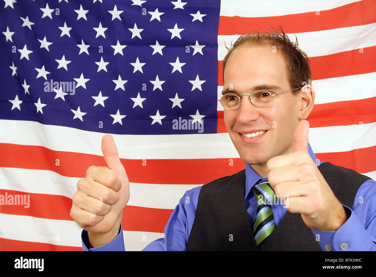 A young businessman jubilation in front of the flag of the United States of America. - Stock Image