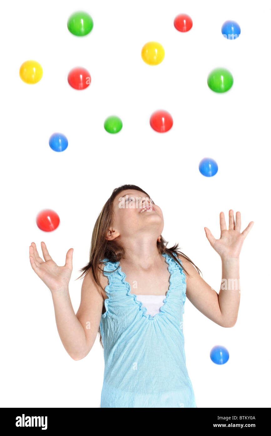 A young girl  catching colored balls. All isolated on white background. - Stock Image