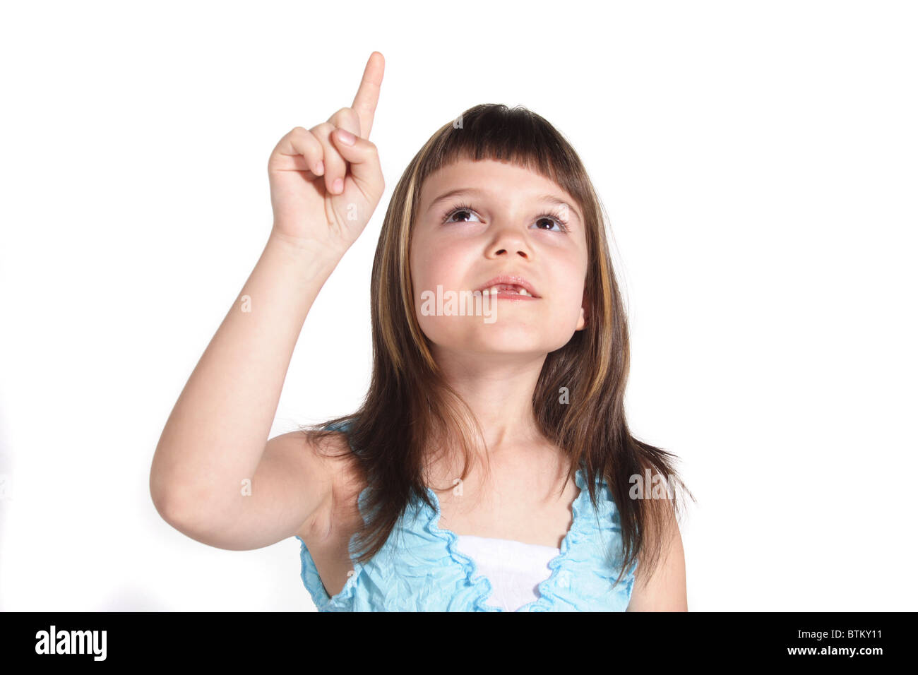 A young girl pointing at something. All isolated on white background. - Stock Image
