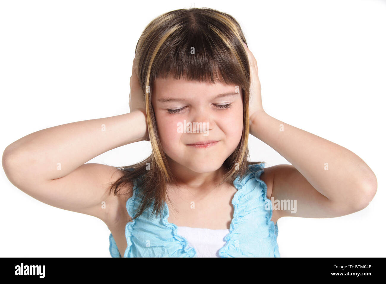 A young girl suffering from noise. All isolated on white background. - Stock Image