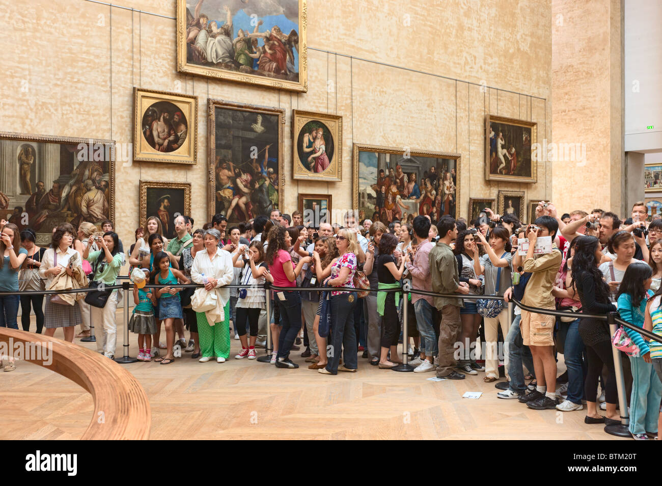 Visitors in front of Mona Lisa Louvre Museum Paris - Stock Image