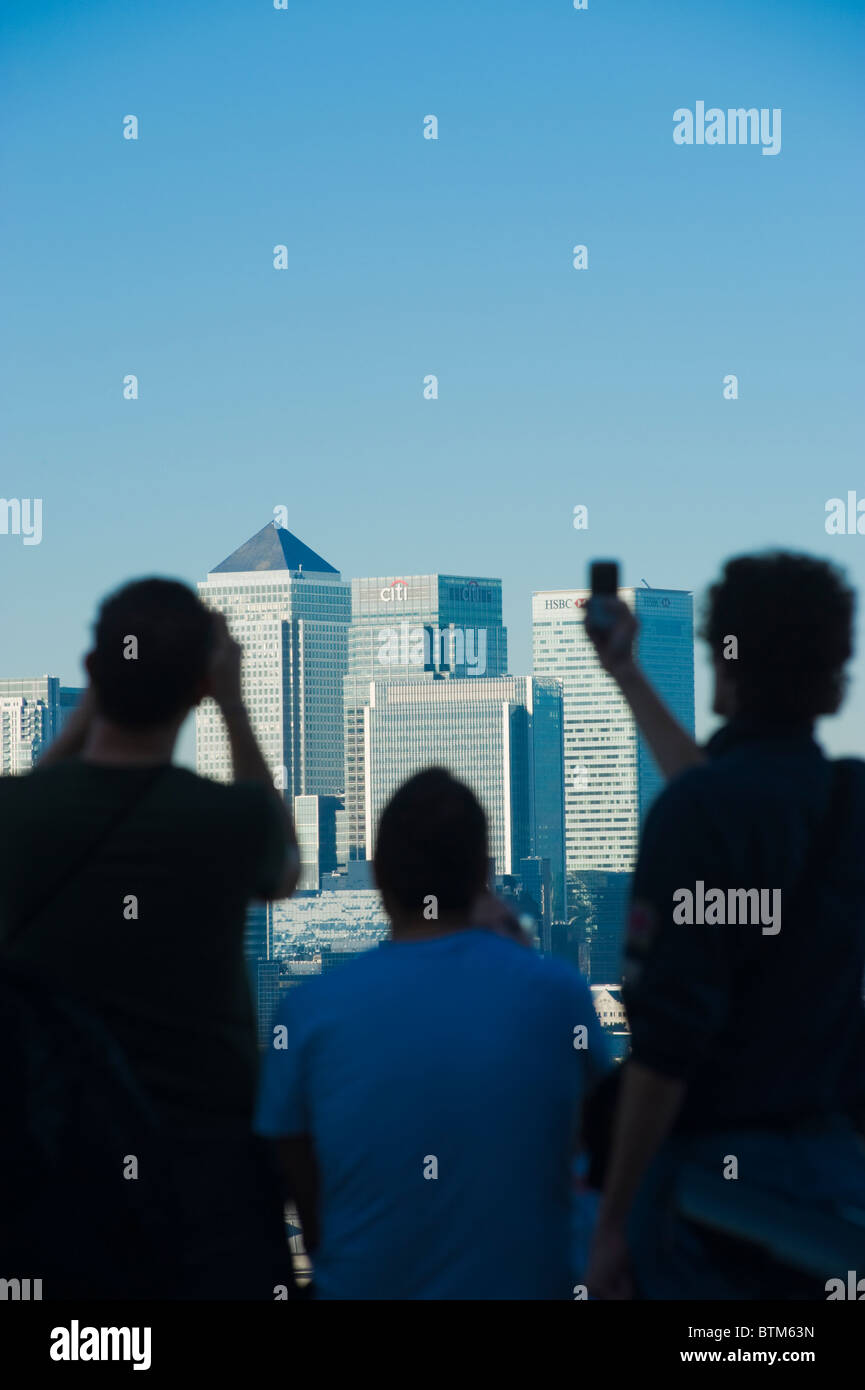 Sightseers in Greenwich Park, London, admiring the view of the skyline of Canary Wharf. - Stock Image
