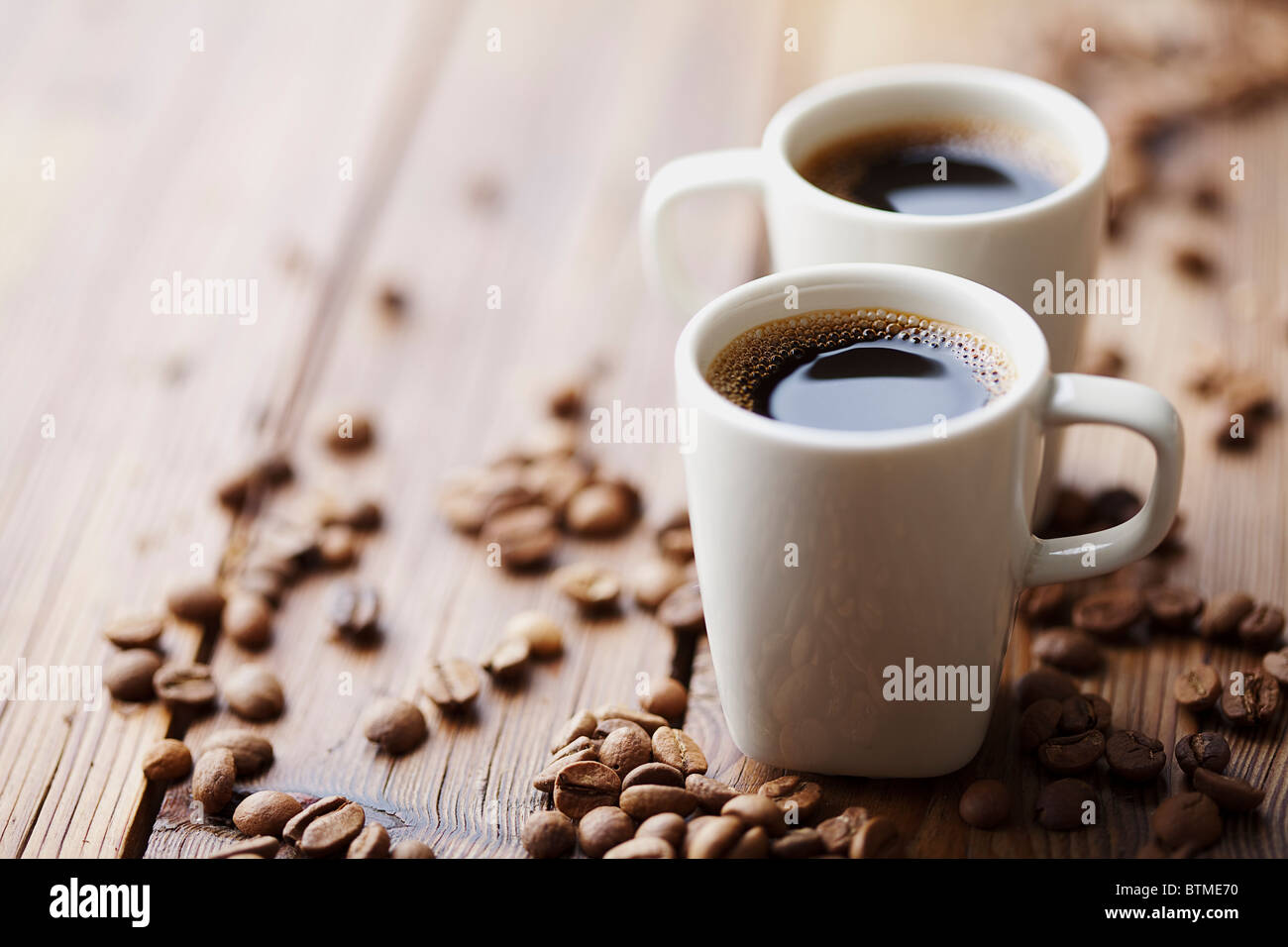 two modern espresso cups on a wooden table - Stock Image