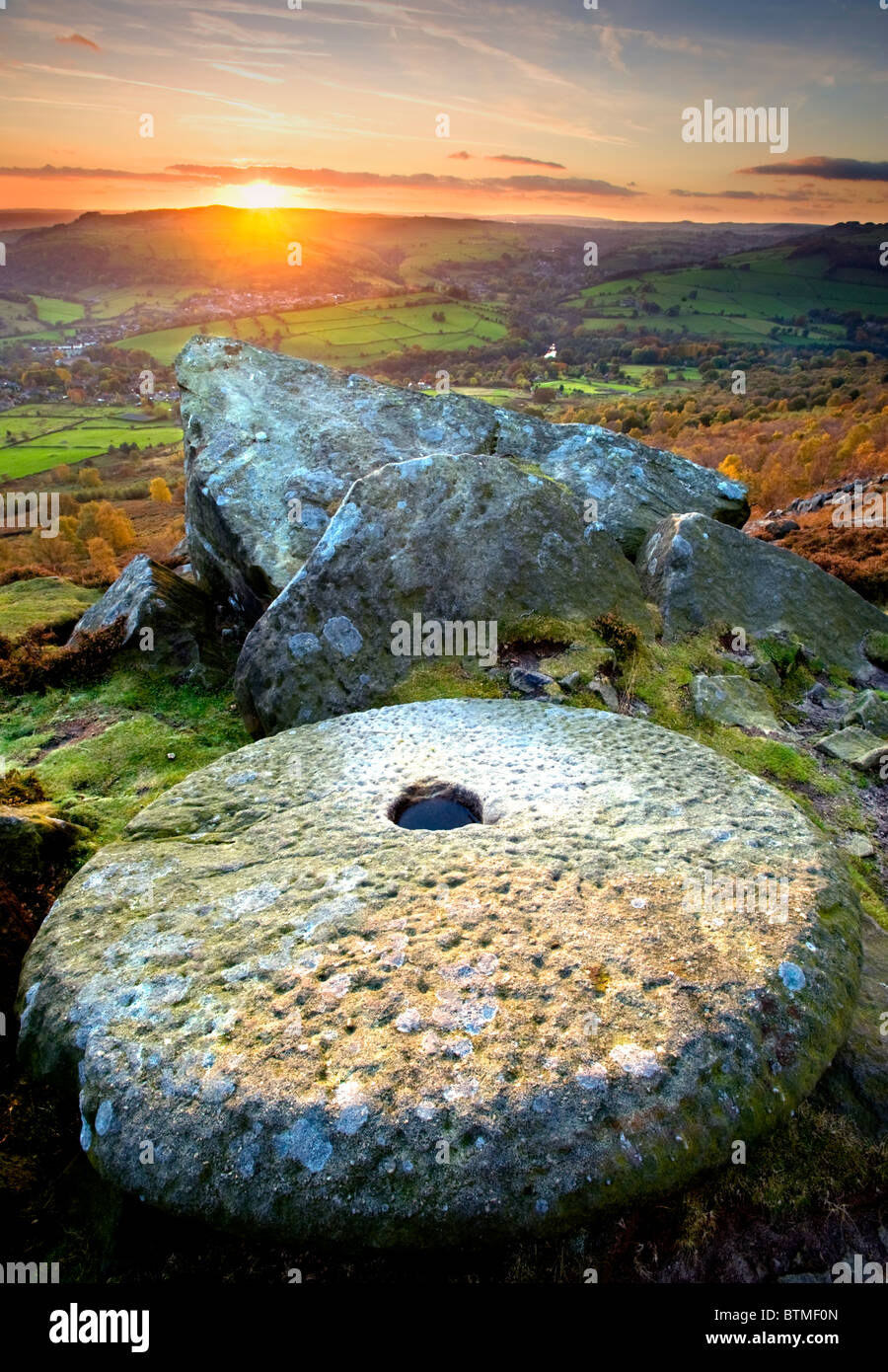 Abandoned Millstone at Sunset on Curbar Edge, Peak District National Park, Derbyshire, England, UK - Stock Image