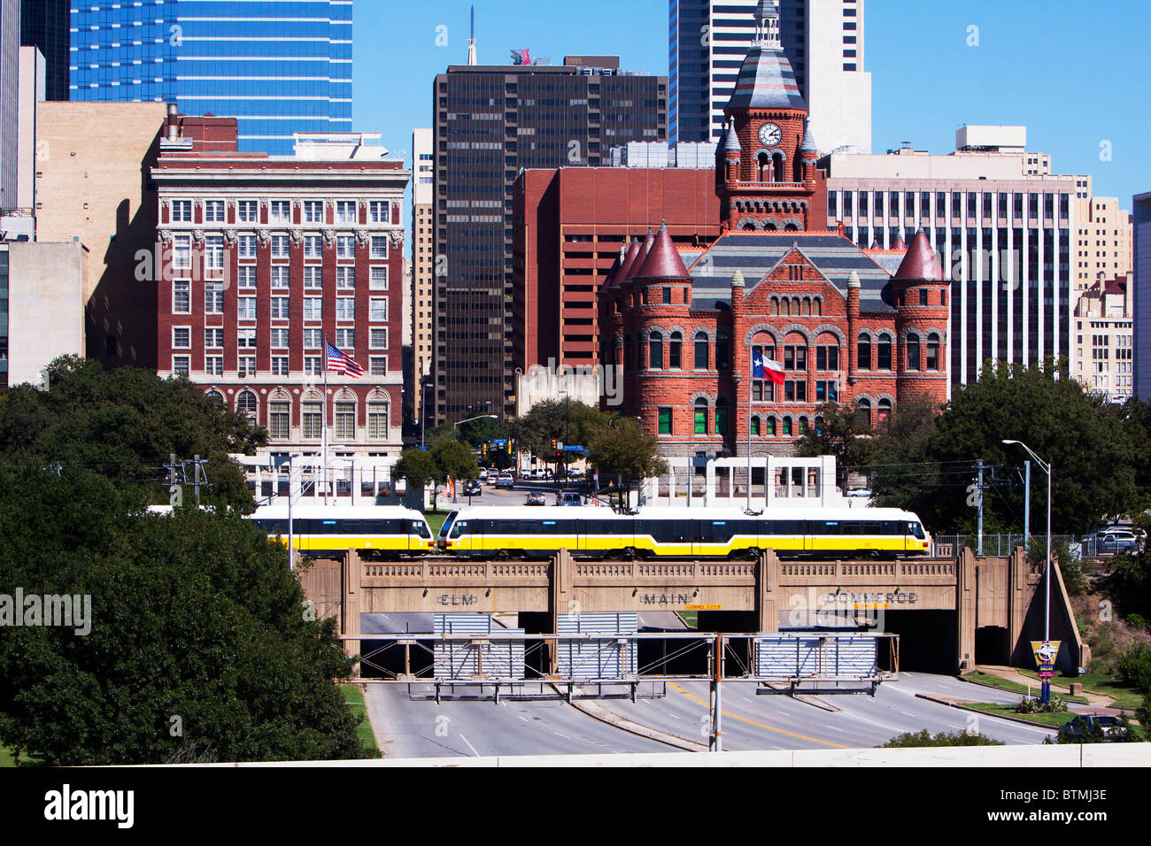 A Dallas Area Rapid Transit (DART) Light Rail train cruises above traffic in downtown Dallas, Texas. - Stock Image