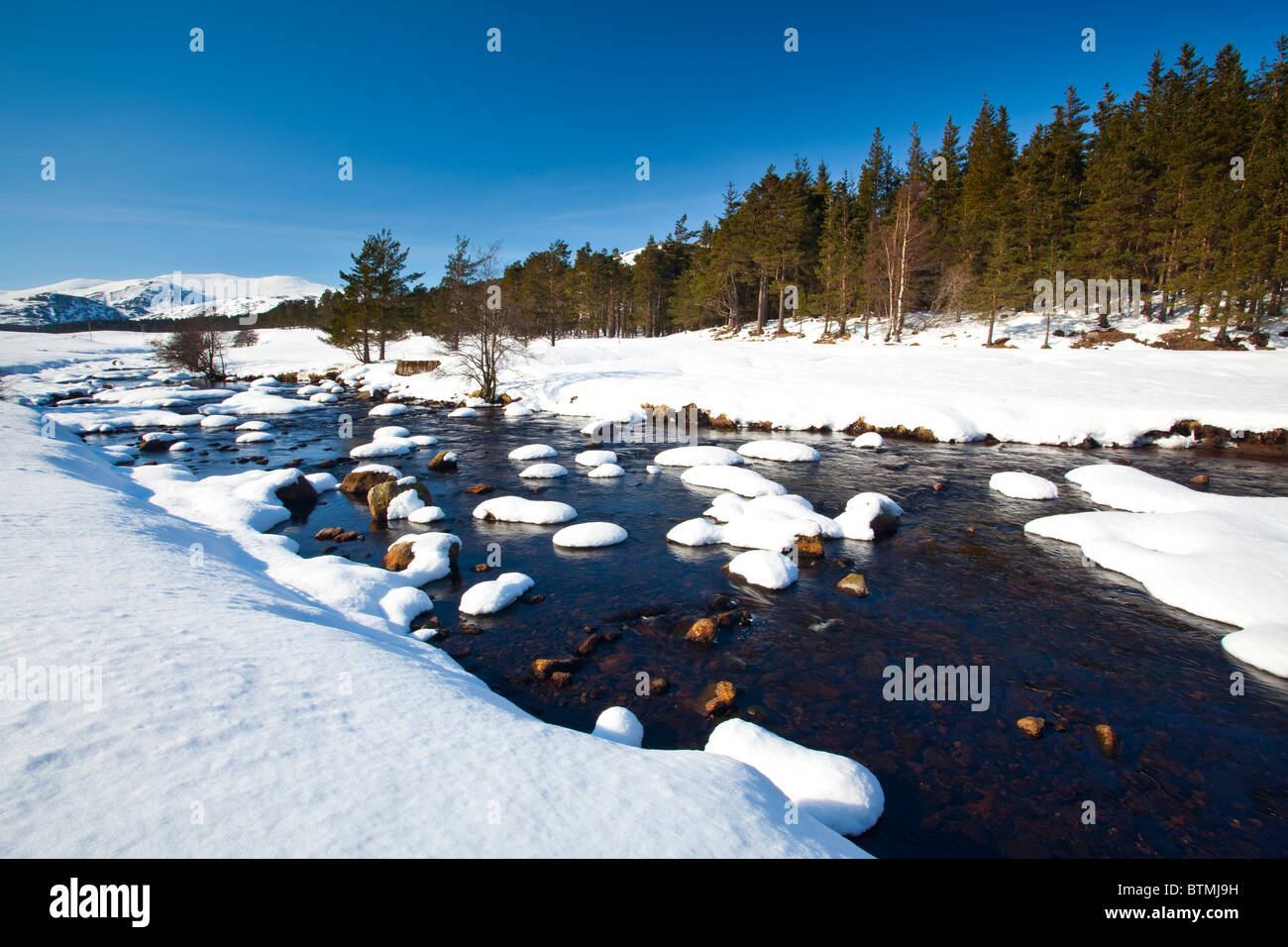 Scotland, Scottish Highlands, Cairngorms National Park. The snow covered River Muick running near a forest  in Glen - Stock Image