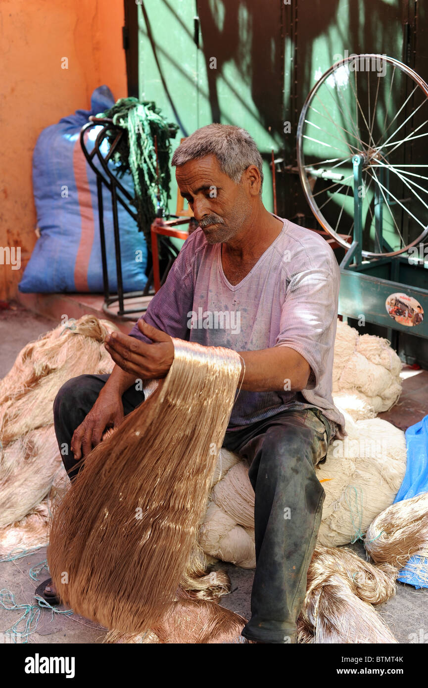 Moroccan with skeins of silvery-gold yarn in the Dyers Market in Marrakesh. - Stock Image