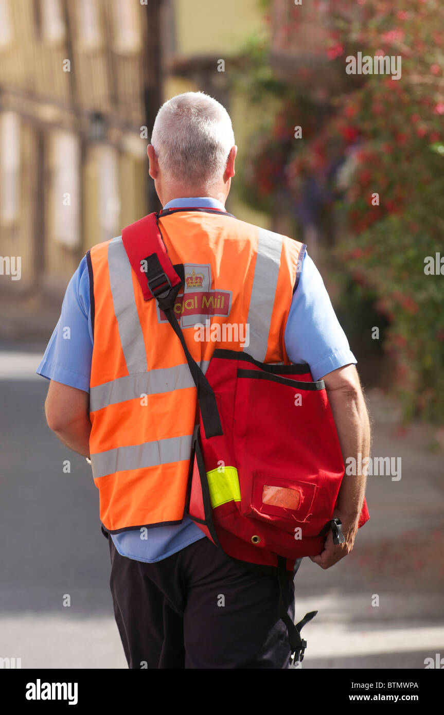 Royal Mail Postman in the Historic Suffolk Village of Lavenham - Stock Image