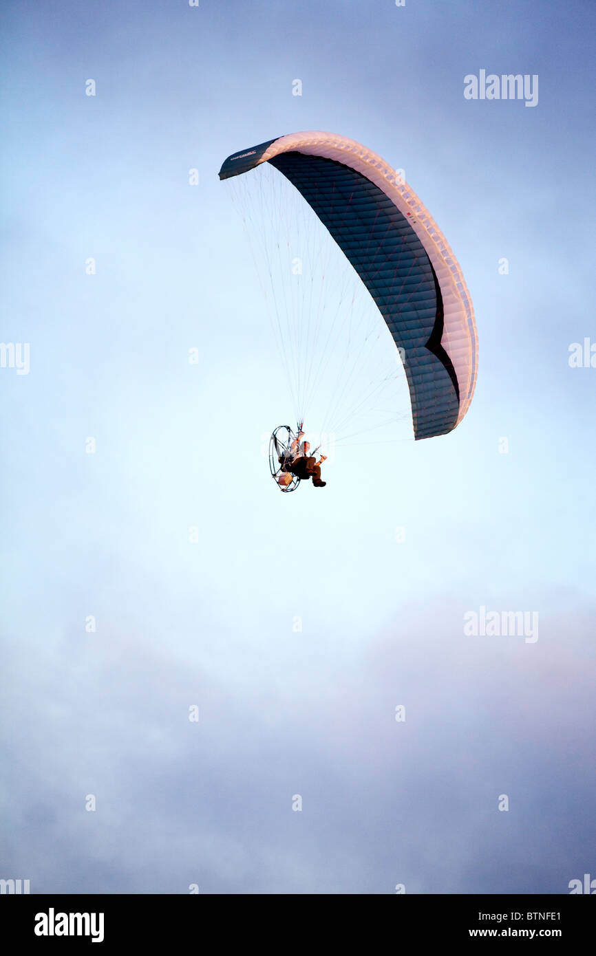 A powered para glider flying overhead at sunset. - Stock Image