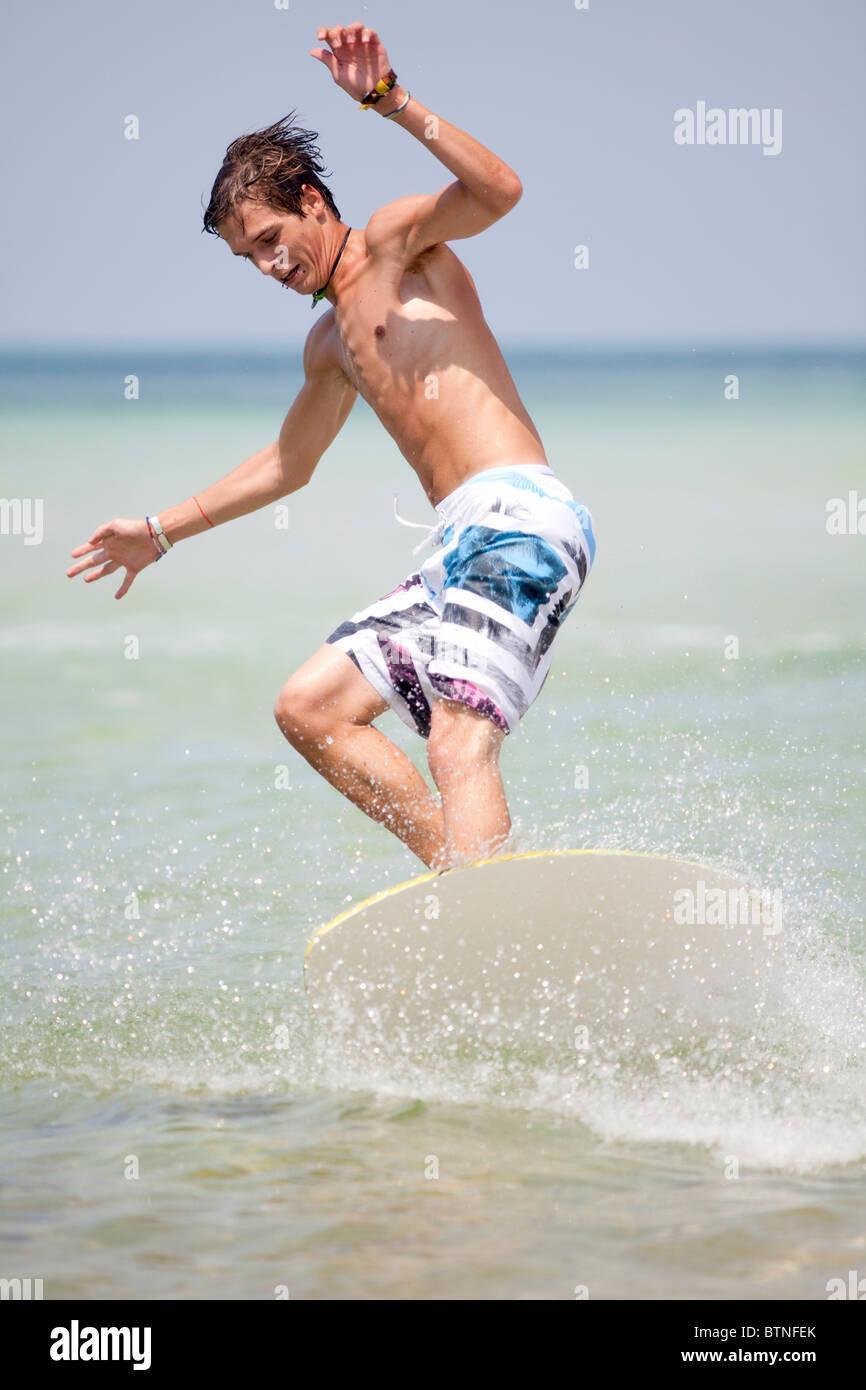 Young man riding a skimboard at the beach. Panama City Beach, Gulf Coast, Florida. - Stock Image