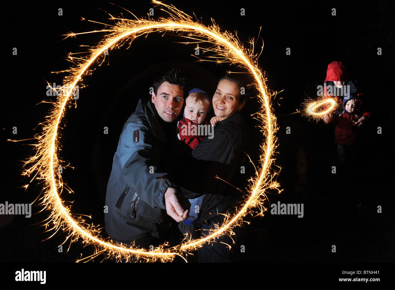 Young couple and child with sparkler on bonfire night Stock Photo