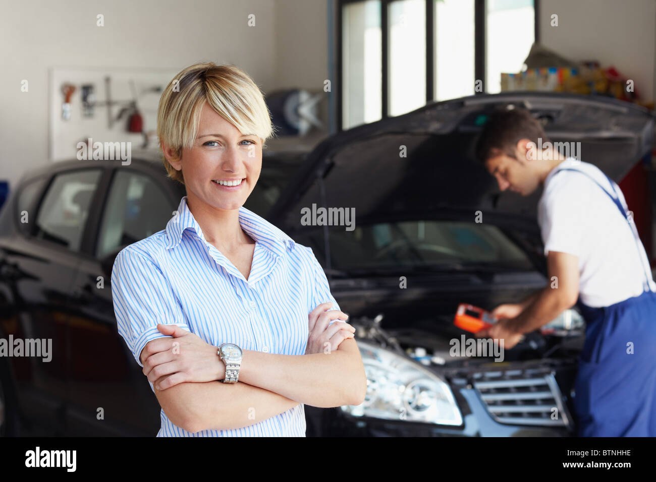 portrait of woman in auto repair shop - Stock Image