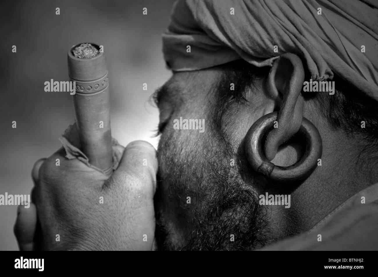 Sadhu smoking the chillum. - Stock Image