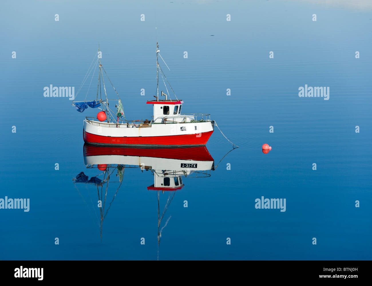 Small red smack, fisherman's boat, on a calm sea. Tromso, North Norway - Stock Image