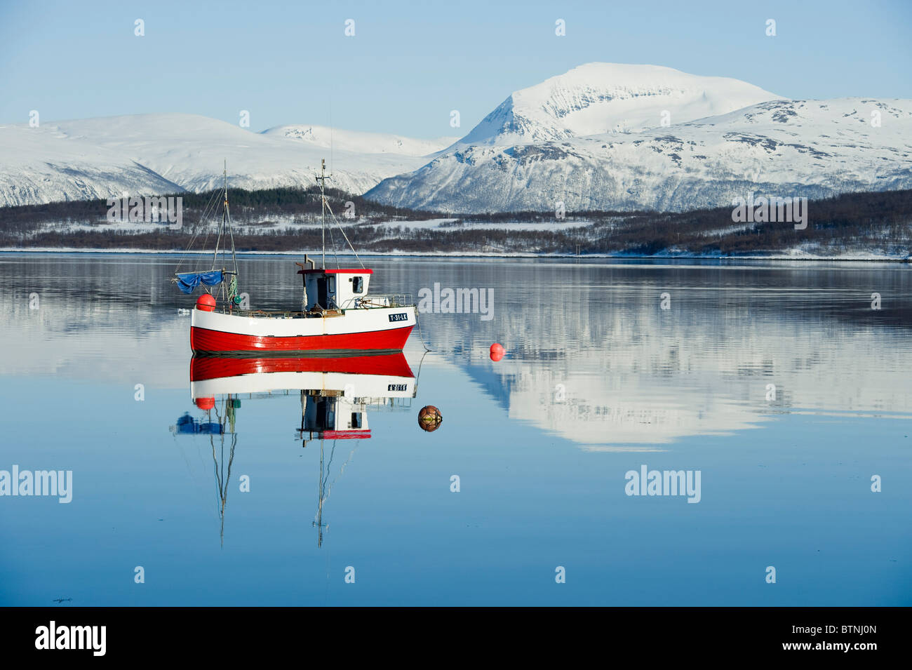 Small red smack, fisherman's boat, on a calm sea. The mountain Tromsdalstinden in the background. Tromso, North - Stock Image