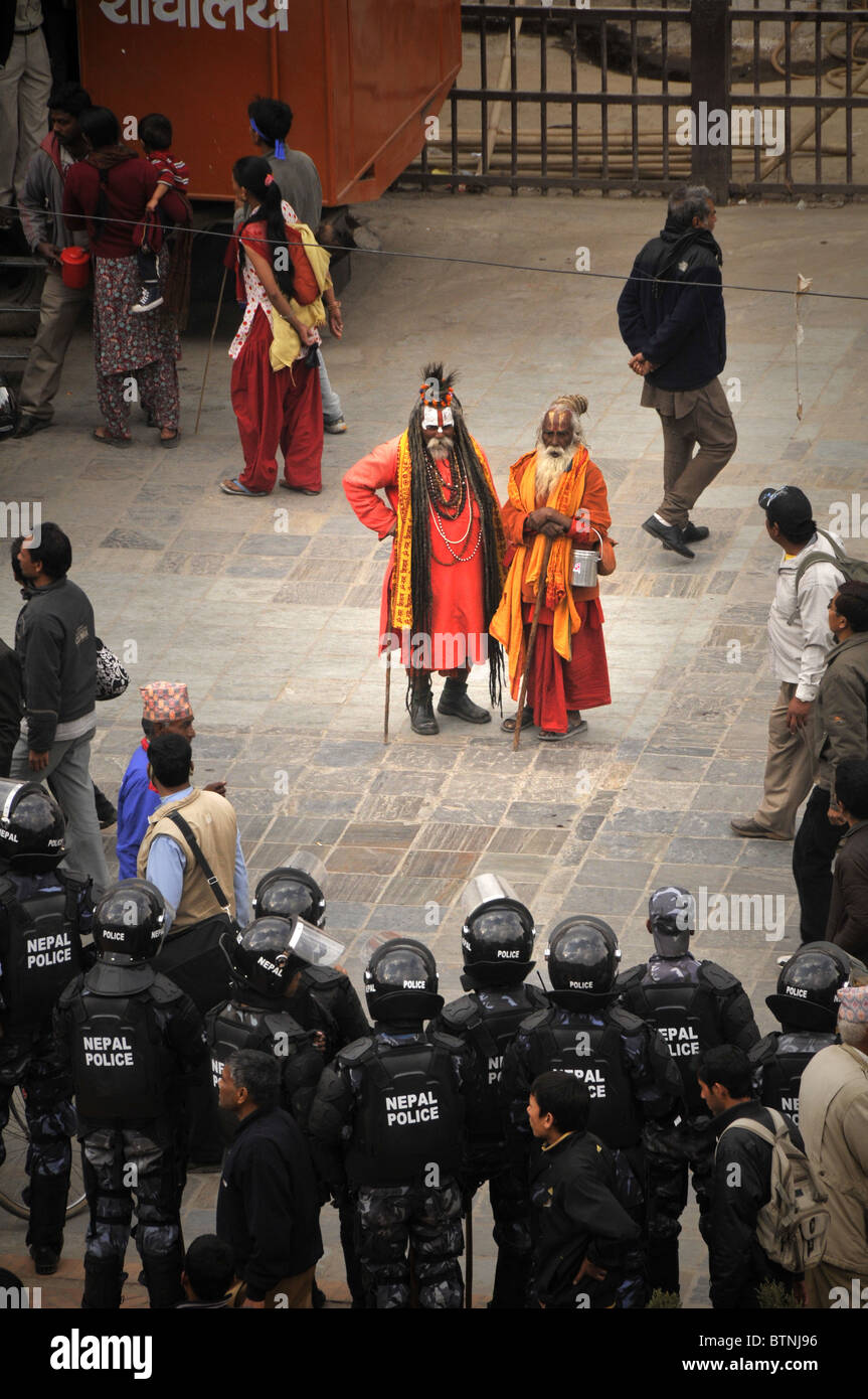 A political demonstration in Kathmandu. The police swarmed the Durban square under the confused eyes of the sadhus. - Stock Image
