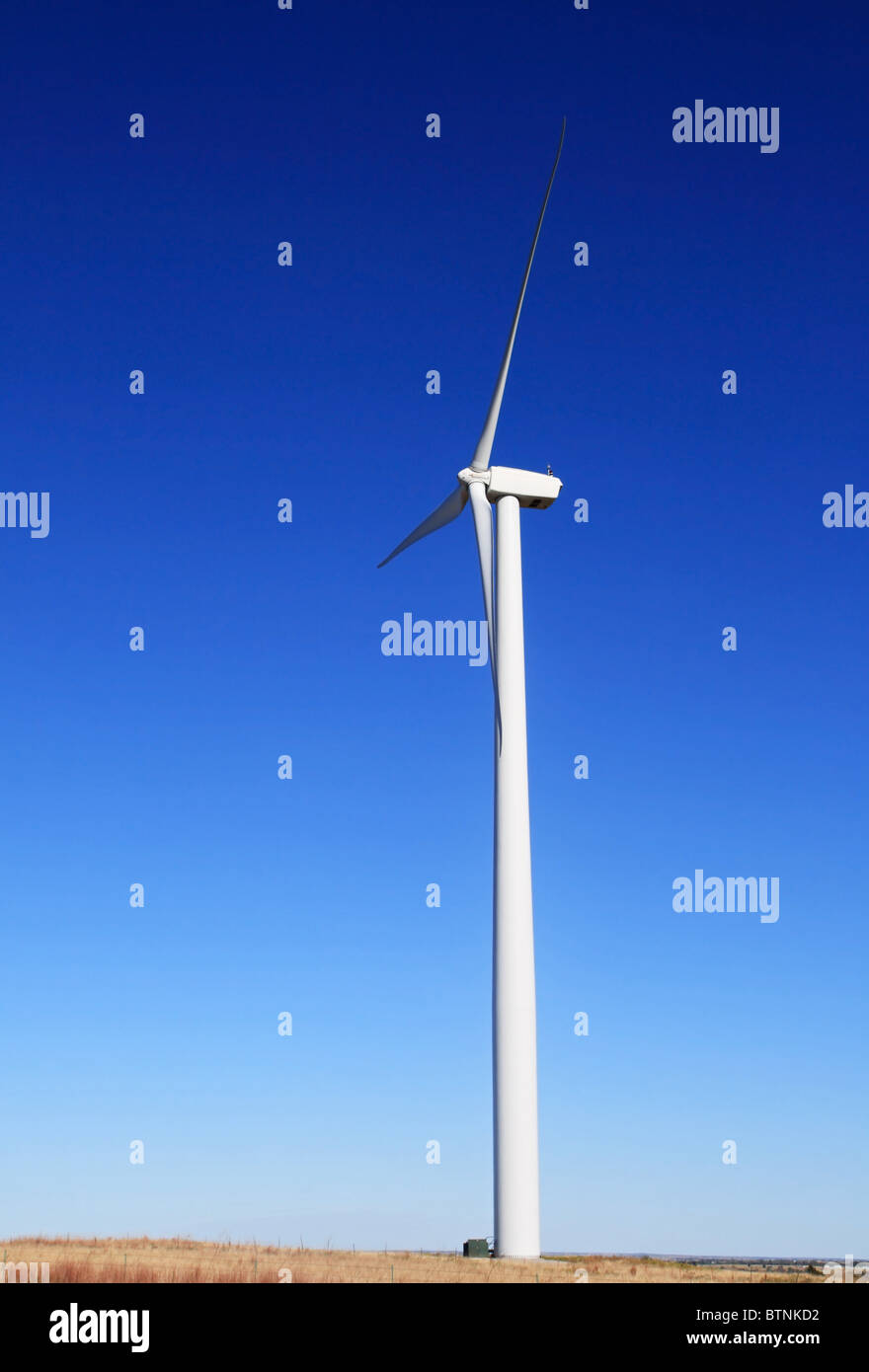 vertical image of tall white electric windmill or wind turbine on a flat prairie with blue sky background - Stock Image